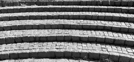 Semicircular steps of the amphitheater. Wide staircase made of stone blocks or bricks. Uneven bricks. The old steps are circular. Monochrome black and white photography.