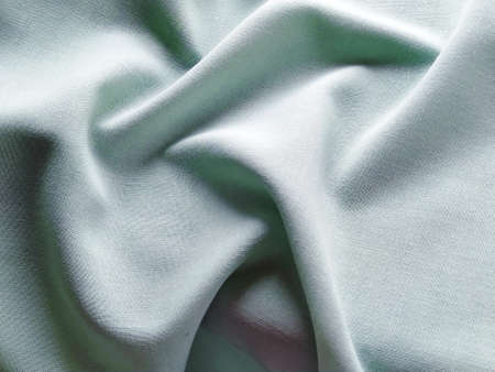 Beautifully folded light green fabric. Soft pleasant waves and flounces on textiles. Close-up. Drapery for curtains, fabric for dressmaking or upholstery.