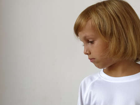 Girl on a white background. The child looks down and to the side at an empty spot where your text might be. Copy space. White T-shirt. Caucasian appearance, blond hair, dark skin. Head side.