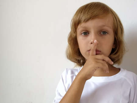 Silence gesture. The finger is near the mouth. The girl on a white background shows a gesture of keeping silence. Child of 7 years old with blond hair. Caucasian type. Copy space. Place for text.
