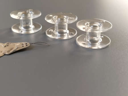 Buttonhole for automatically threading the sewing machine needle. Three transparent plastic sewing machine bobbins. Textile industry. Detail of sewing equipment. Gray background, back lighting.