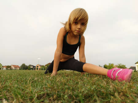A 6-7 year old girl goes in for sports at the stadium. A child in sportswear in black and bright pink sneakers. Exercise for stretching the muscles of the legs Split. Caucasian girl with blond hair.