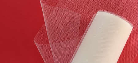 Fabric - white mesh in a roll on a red background. Nylon tape for tying bows on hair. A skein of tulle fabric. Copy space. Stock Photo