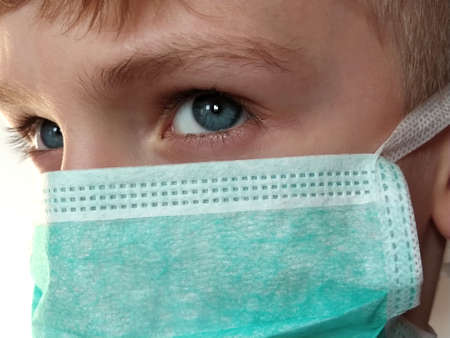 Masked child. The face of a 7-year-old boy in a protective surgical mask close-up. Schoolboy with blond hair and blue-gray eyes on white background.
