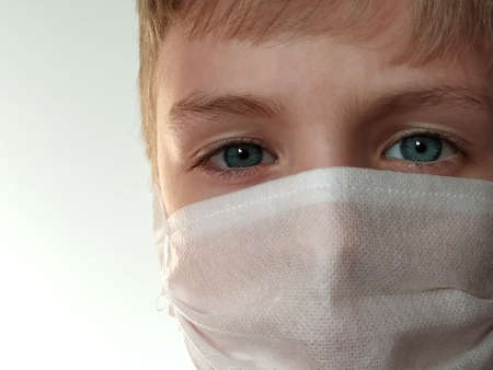 Masked child. The face of a 7-year-old boy in a protective white surgical mask close-up. Schoolboy with blond hair and blue-gray eyes on white background