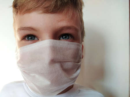 Masked child. The face of a 7-year-old boy in a protective white surgical mask close-up. Schoolboy with blond hair and blue-gray eyes on white background. 版權商用圖片
