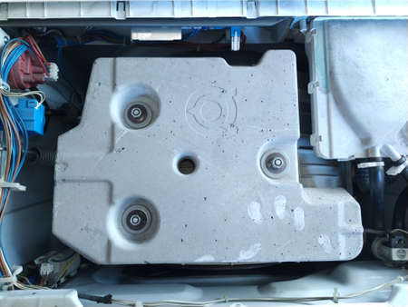 Inside of the washing machine - top view. Drum, centrifuge and home appliance parts. Washing machine cover removed. Plastic and metal parts, rubber hoses. Master's fingerprints.