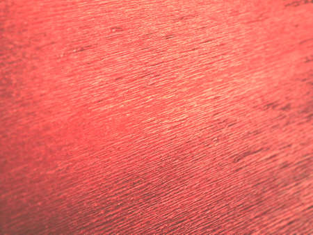 Corrugated paper in red. Uneven surface. Abstract background. Wavy edges of the paper sheet. Lighting gradient.