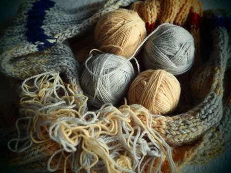 Knitting a scarf or sweater from gray, beige and orange yarns. Balls of woolen and acrylic threads. Knitting as a hobby. Accessories, knitting needles, crochet hooks