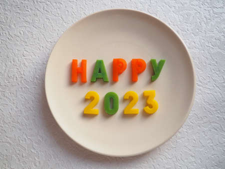 Happy 2023. Happy New Year greetings. New Year's postcard. The white plate is lined with orange, green, yellow letters and numbers. Flat lay. Objects on a horizontal surface.