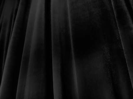 Soft waves on black velvet curtains. Stylized defocused image. Dark draperies made of pleasant fabric. Pleats on the curtains. Abstract black and gray background