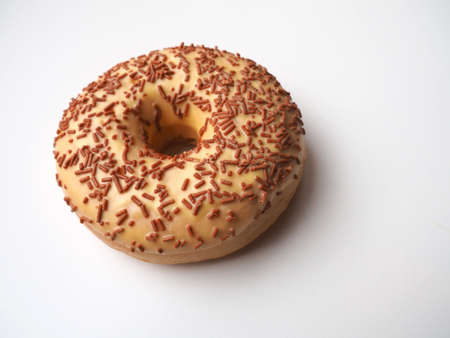 A doughnut or donut. A type of leavened fried dough. Sweet snack that can be homemade or purchased in bakeries, supermarkets, food stalls. Delicious pie with light icing on a white background.