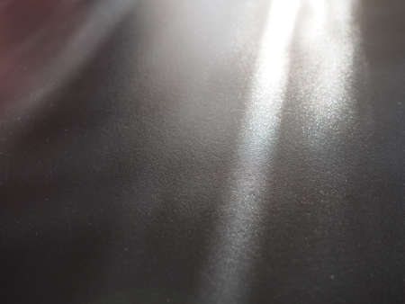 Illumination rays on gray surface. Abstract rays of light and lens flare on a gray background. Vertical, horizontal and diagonal light stripes.