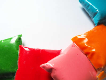 Colorful kid's plasticine on white background, Colorful dough modeling clay. Packing of colored soft plasticine in plastic bags. Copy space. Stock fotó