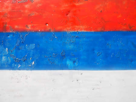 Serbian flag, tricolor red, blue, white painted on a metal surface. Peeling paint. Stock fotó