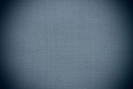 texture of natural blue fabric close-up. The texture of the fabric is made of natural cotton or linen textile material. blue canvas background. Smooth surface, smoothed fabric. Dark vignetting Stock fotó