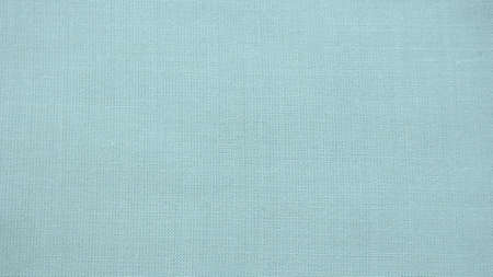 texture of natural light green or blue fabric close-up. The texture of the fabric is made of natural cotton or linen textile material. Green canvas background. Smooth surface of mint-colored fabric.