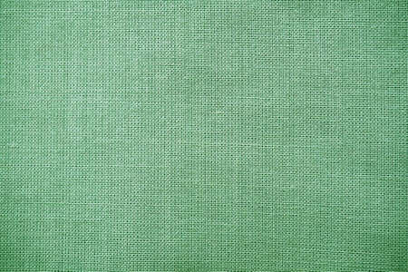 texture of natural green fabric close-up. The texture of the fabric is made of natural cotton or linen textile material. Green canvas background. Smooth surface, smoothed fabric.