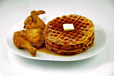 Fried chicken and waffles with maple syrup and butter on a white plate and shot on a white background