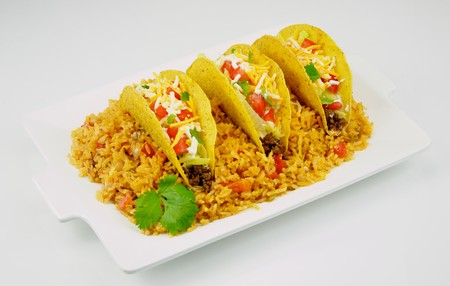 Tacos served on a bed of Spanish rice garnished with fresh cilantro.