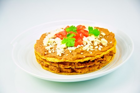 Traditional tostada topped with refried beans, queso fresco, vine ripe tomatoes, and fresh cilantro