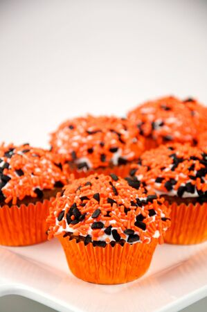 A Chocolate Cupcake with Halloween Sprinkles in a orange foil wrapper Stockfoto