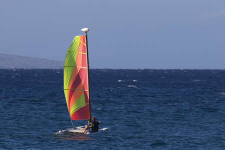 A couple sail on the deep blue Pacific on a catamaran with a brightly coloured sail.
