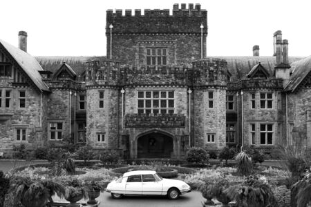 streamlined: A white, 1968 Citro�n DS, the classic, elegant, streamlined French automobile, stands in front of a stone castle.