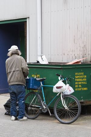 he old: A middle aged man, with grey hair and torn, baggy clothes, stands by his old bicycle and the dumpster where he has been searching for bottles.