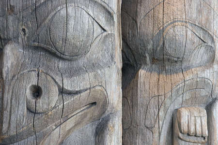 northwest indian art: Detail of two faces on a pair of old, worn, unpainted, wooden West Coast Indian totem poles in a Vancouver, British Columbia park.