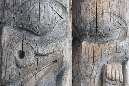 totem indiano: Dettaglio di due facce su una coppia di anziani, indossati, unpainted, legno West Coast totem indiano poli in uno Vancouver, British Columbia parco. Archivio Fotografico
