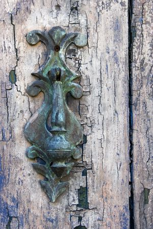 An old door knocker, green with age, on an old worn, wooden door.  版權商用圖片