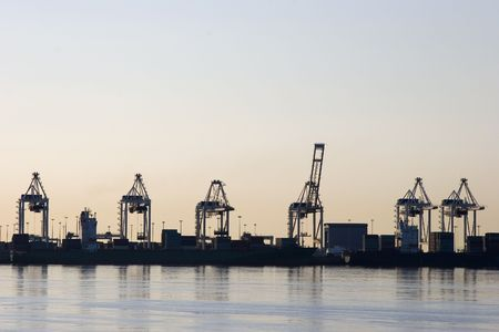 A row of container port cranes silhouetted against an evening sky. Stock Photo - 951054