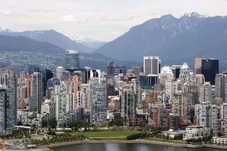 treed: The downtown highrise area of Vancouver, British Columbia, Canada, fronted by a park and the shoreline of False Creek, backed by the treed and snow capped coastal mountains.