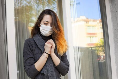 Sick woman staying at home and praying for protection from coronavirus wearing a disposable medical mask on her face.
