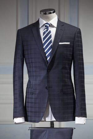 Traje de hombre azul marino y corbata azul y blanca a rayas aislado sobre fondo blanco.