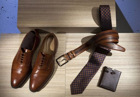 Men's accessories collection. Classic brown shoes, brown belt, chic tie and wallet. Men's wear.