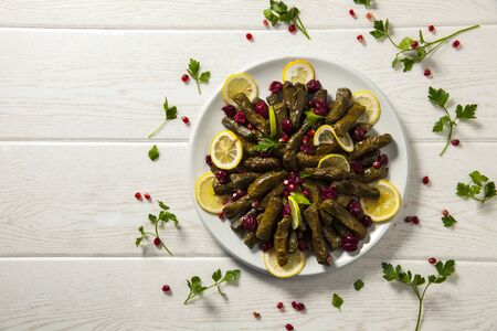 Stuffed vine leaves. Cherry and lemon leaf wrapping, stuffed. Traditional Turkish stuffed leaf wrapper. Decorated with cherry, lemon, parsley and pomegranate seeds. Wooden pattern on white background.