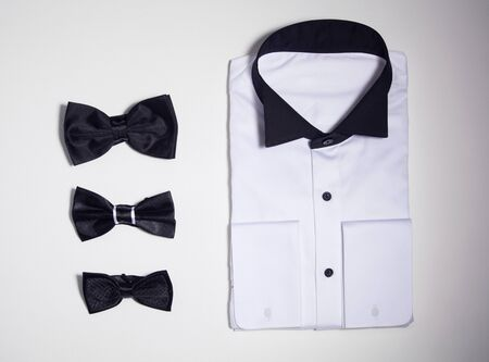 Folded shirt and black bow ties isolated on white background.