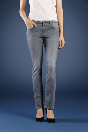 Young fashion woman's legs in jeans and stiletto shoes on blue background