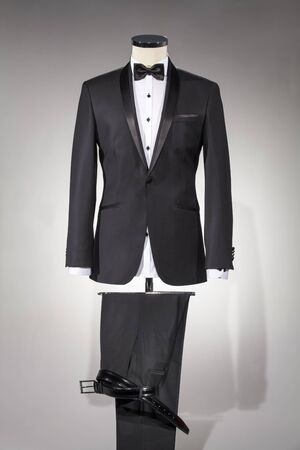 Male clothing, suit on stand. Men's black suit and white shirt and black bow tie, classic men's shoes and belt isolated on white background. Tuxedo.