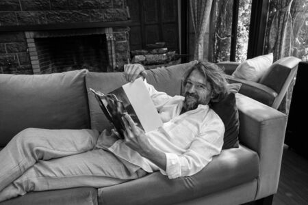 Man in a white shirt. Spending time at home and relaxing. Lying down on the couch, having a good time, reading funny content on the magazine. Looking at camera and laughing, smiling. Фото со стока