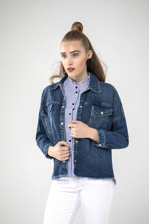 cute model posing in white jeans, blue striped shirt and cool jean coat. white background.