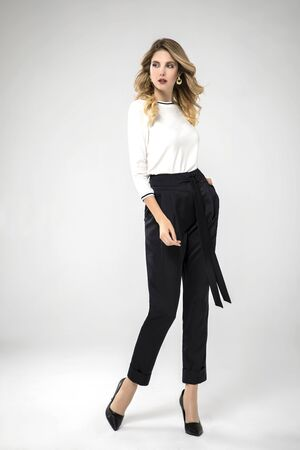 blonde model posing in her black chic pants and white blouse. white background. studio shot. standing.