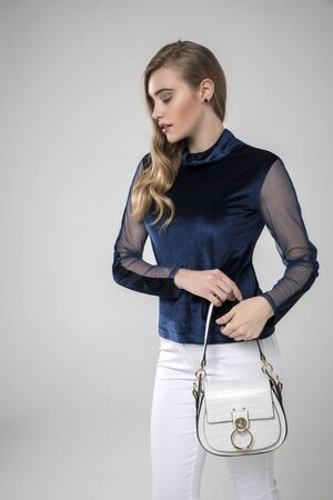 beautiful blonde model in night blue top and stylish white pants. leather handbag. white background. Reklamní fotografie