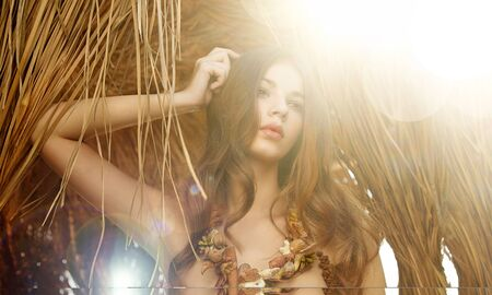 wearing a handmade sea shell necklace. Beautiful woman with long brown hair posing under sunlight.