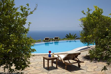 A swimming pool with a sea view in a wonderful garden. Cocktail with red flower on the coffee table and sunbed next to it. Stok Fotoğraf