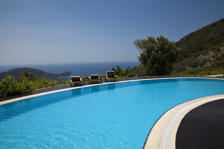 Swimming pool in the garden. Beautiful sea and mountain landscape. Stok Fotoğraf