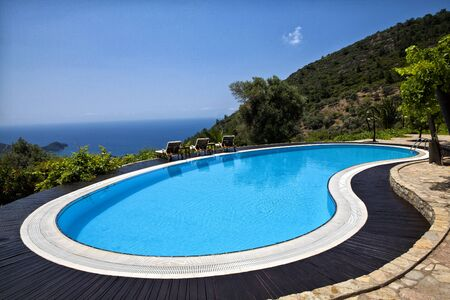 Swimming pool in the garden and beautiful sea and mountain landscape with trees.