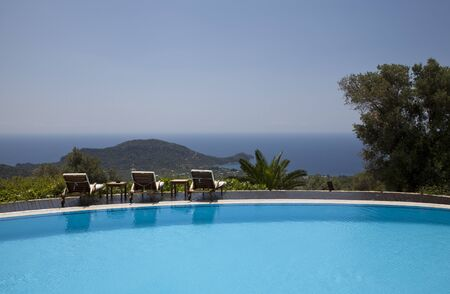 Swimming pool in the garden and beautiful sea and mountain landscape with trees and empty lounge chairs.